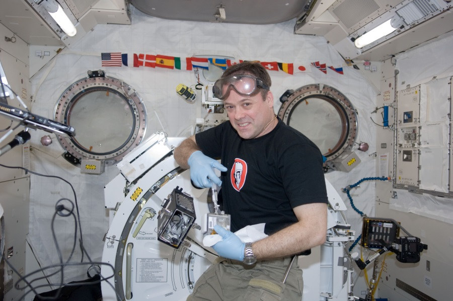 Image: Astronaut Dr Jon Garan watering cucumber seedlings on board the ISS. Credit JAXA, NASA.